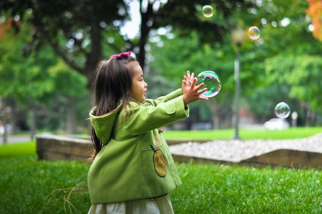 NIña jugando con burbujas. Terapia para los niños.
